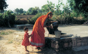 a woman collecting water rom a well in Rajastan