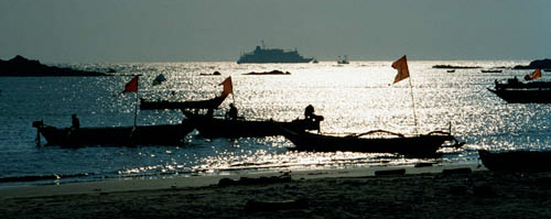 Silhouette of ship with Hodi boats